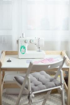 Jak szyć maskę, proces szycia maski ochronnej, kawałki kropkowanej tkaniny, nici i maszynę do szycia na białym stole z białym krzesłem.