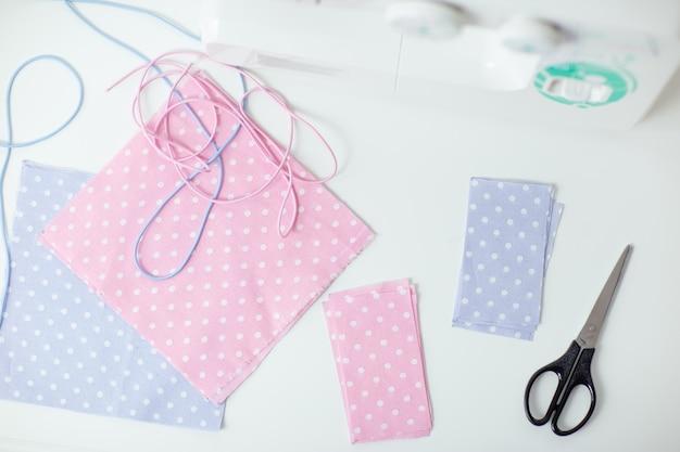 Jak szyć maskę, proces szycia maski ochronnej, kawałki kropkowanej tkaniny, nici i maszynę do szycia na białym stole.
