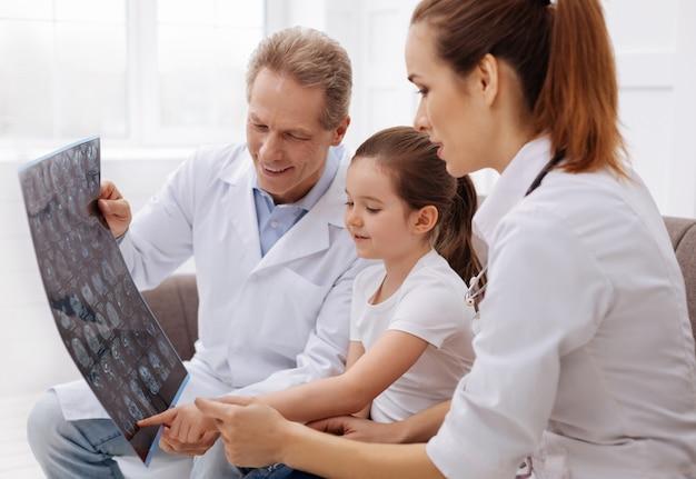 Jak to nazywasz. mądra zainteresowana śliczna dziewczyna chcąca dowiedzieć się kilku rzeczy podczas wizyty u lekarza i oglądania rezonansu magnetycznego mózgu