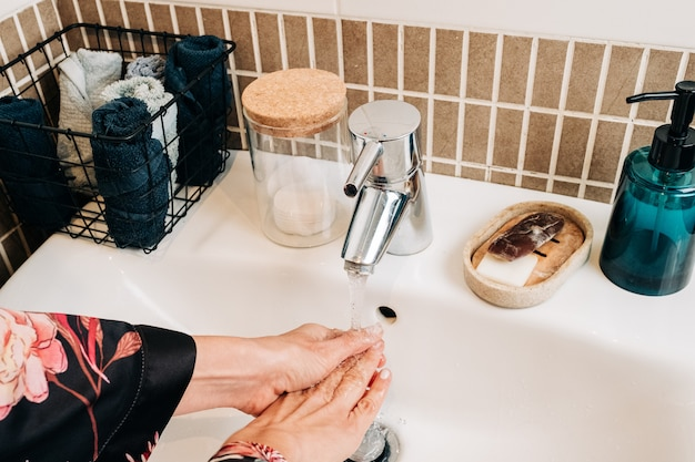 Jak umyć ręce, aby zapobiec koronawirusowi. kobieta do mycia rąk w domu