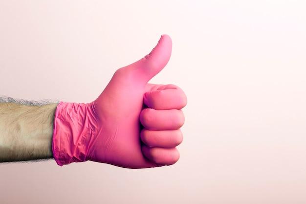 """""""jak"""" w rękawicy medycznej. ręka lekarza w różowej rękawicy medycznej na jasnym tle."""