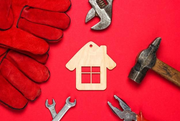 Jak zbudować dom? narzędzia do pracy dla majsterkowiczów i figurka mini domku na czerwonym tle