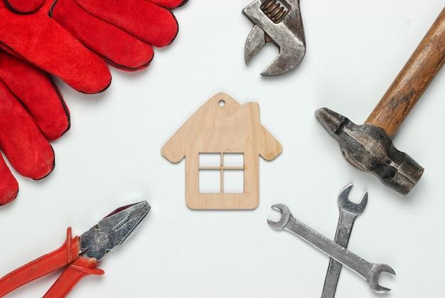 Jak zbudować dom? narzędzia do pracy dla majsterkowiczów i figurka mini domu na białym tle
