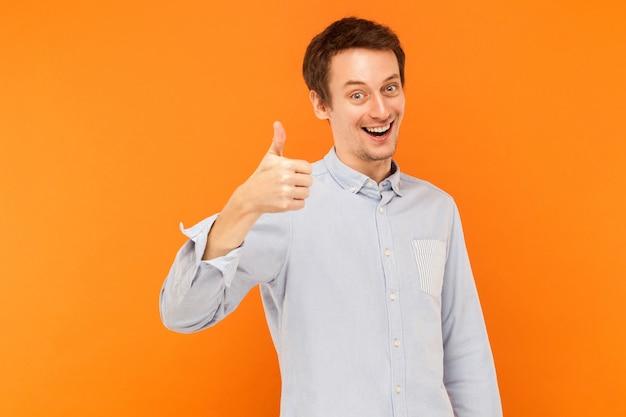 Jak znak uśmiechnięty mężczyzna kciuki w górę i patrzący w kamerę