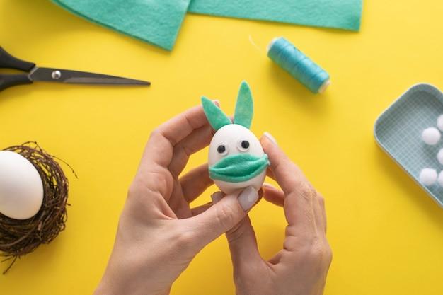 Jak zrobić króliczka z filcu do dekoracji wielkanocnych i zabawy. koncepcja diy. instrukcja krok po kroku. krok 13. przyklejamy uszy do króliczka.