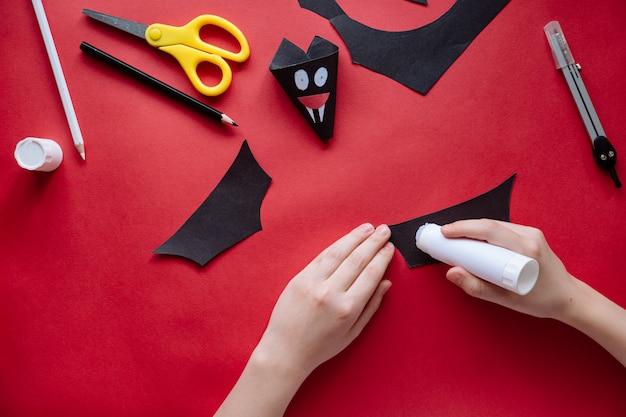 Jak zrobić nietoperza z papieru w domu. ręki robi rzemiosłu z papieru. instrukcja fotografowania krok po kroku. krok 10. przyklej skrzydła. projekt artystyczny dla dzieci.