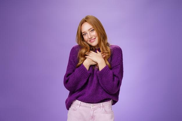 Jakie słodkie dzięki. delikatna urocza ruda dziewczyna w fioletowym swetrze trzymająca się za ręce na sercu przechylająca głowę zalotna i szczęśliwa, jak uśmiecha się do kamery wdzięczna i wzruszona romantycznym prezentem na fioletowej ścianie.