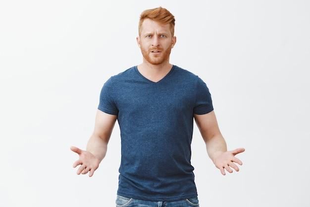 Jakiś problem. portret zdezorientowanego, atrakcyjnego, męskiego rudowłosego europejczyka w niebieskiej koszulce, gestykulującego dłońmi w niezrozumiałej pozie, czekającego na wyjaśnienie nad szarą ścianą