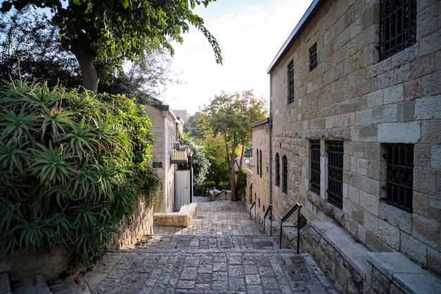 Jakiś zabytkowy pas malowniczego miasteczka na bliskim wschodzie. regularne życie starego europejskiego miasteczka. wąska ulica z kamiennymi budynkami i zielonymi drzewami. stare miasto schody prowadzące w pogodny dzień.
