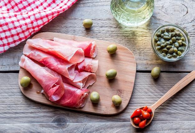 Jamon z kaparami i oliwkami na desce