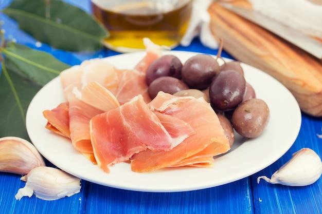 Jamon z oliwkami na bielu talerzu