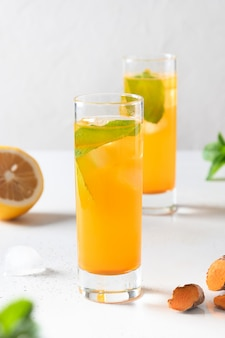 Jamu indonezyjski ziołowy napój z naturalnymi składnikami kurkuma, imbir, cytryna na białym tle. ścieśniać.