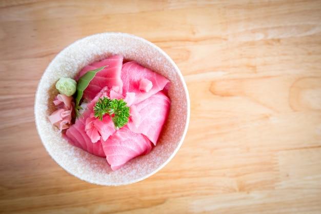 Japan food tuńczyk lub maguro don składa się z pokrojonego w plasterki tuńczyka lub maguro na wierzchu japońskiego ryżu. podawane z wasabi i marynowanym imbirem w białej misce na drewnianym stole.