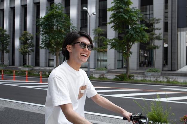 Japończyk z rowerem na zewnątrz