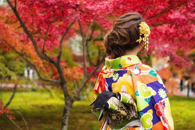 Japonka w kolorowym kimonie cieszy się jesiennymi czerwonymi klonowymi ogrodami w świątyni nanzen-ji, kioto