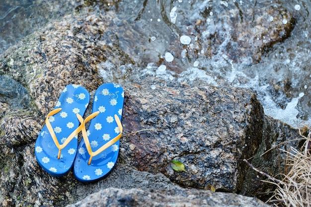 Japonki pozostawione na skale nad wodą, koncepcja czasu letniego