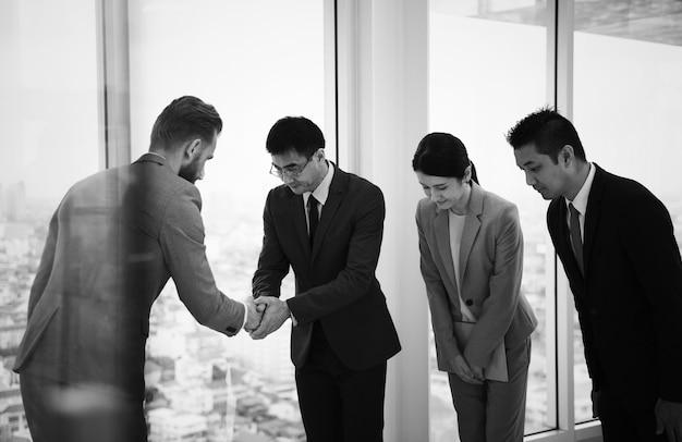 Japońscy biznesmenów ludzie ma uścisk dłoni z kolegą