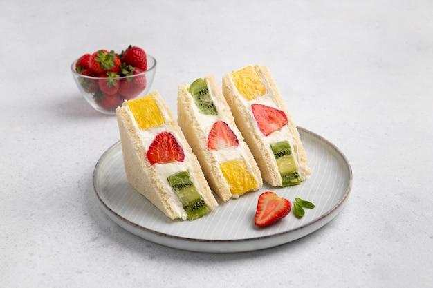 Japońska kanapka ze słodkimi owocami z truskawką, ananasem i kiwi. słodkie domowe śniadanie letnie