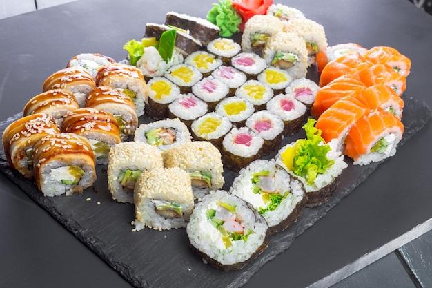 Japońska restauracja, sushi roll na czarnej płycie łupkowej.