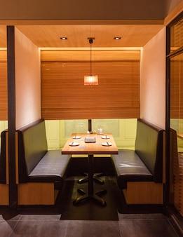 Japońska restauracja yakitori z grillowanym szaszłykiem prywatna część wypoczynkowa. przeważnie ozdobiony fakturą drewna dębowego. minimalistyczny wystrój wnętrz.