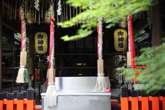 Japońska świątynia z japońską czerwoną bramą i zielonymi liśćmi klonu w kioto w japonii
