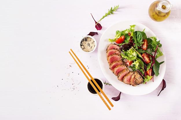 Japońska tradycyjna sałatka z kawałkami średnio rzadkiego grillowanego tuńczyka ahi i sezamu z sałatką ze świeżych warzyw na talerzu