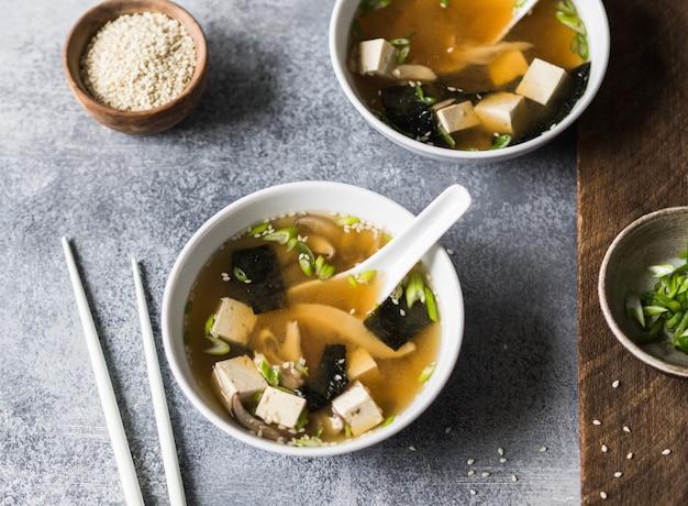 Japońska zupa miso z boczniakami w białej misce z łyżką i białymi pałeczkami na szarym i drewnianym tle.
