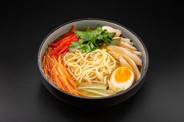 Japońska zupa ramen z filetem z kurczaka i makaronem jajecznym, z jajkiem kurzym, selerem i papryką.