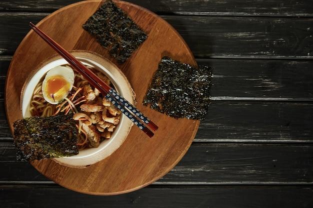 Japońska zupa ramen z kurczakiem, jajkiem, czosnkiem i makaronem na ciemnym drewnie