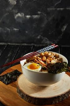 Japońska zupa ramen z kurczakiem, jajkiem, czosnkiem i makaronem na ciemnym tle drewnianych. azjatycki makaron miso ramen.