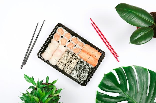 Japoński catering gastronomiczny. sushi z pałeczkami, na białej powierzchni na wynos