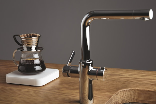 Japoński ekspres do kawy kroplowy na prostych białych obciążnikach za srebrnym kranem w kawiarni na grubym drewnianym stole.