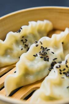 Japoński gyoza w tradycyjnym parowcu, żółte pałeczki