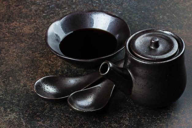 Japoński i chiński sprzęt spożywczy na tle ciemnego kamienia betonu tabeli. łyżki, kubek z sosem sojowym i czajnik.