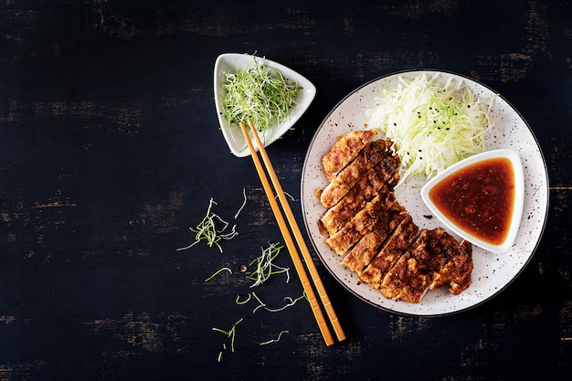 Japoński kotlet z kapustą i sosem tonkatsu. .
