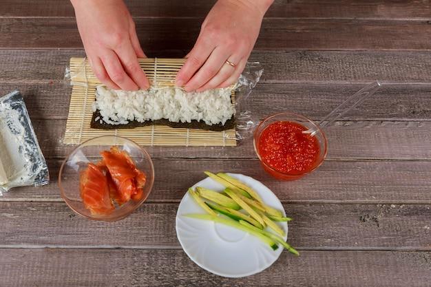 Japoński kucharz robi sushi łososia - japońskie jedzenie