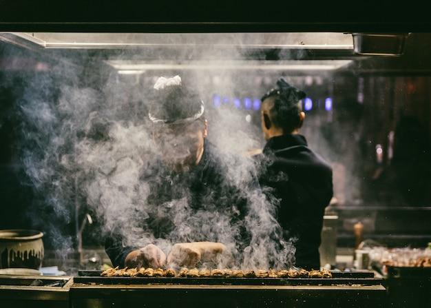 Japoński kucharz yakitori grilluje kurczaka z dużą ilością dymu.