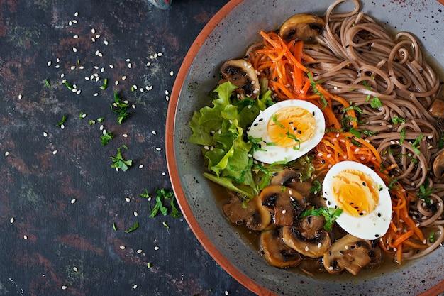 Japoński makaron ramen z miso z jajkami, marchewką i grzybami. zupa pyszne jedzenie. leżał płasko. widok z góry