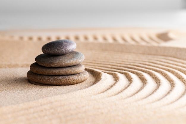 Japoński ogród zen z kamieniem w zgrabionym piasku