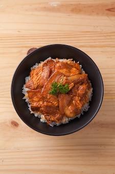 Japoński pikantny brzuch wieprzowy miska ryżu na stole z drewna
