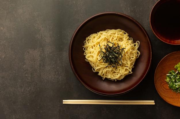 """Japoński ramen na zimno lub """"zaru soba"""" z posiekaną zieloną cebulą, tartym wasabi i filiżanką do zanurzenia sosu widok z góry"""