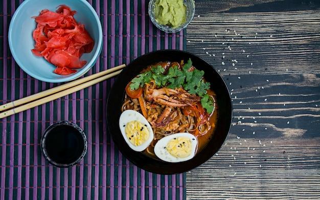 Japoński ramen z owocami morza, ziołami i marynowanymi jajkami na ciemnej powierzchni