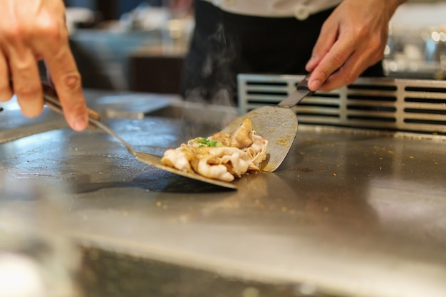 Japoński szef kuchni gotuje mięso w restauracji teppanyaki