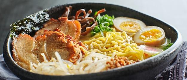 Japoński tonkotsu ramen puchar na obiadowym stole przy restauracją
