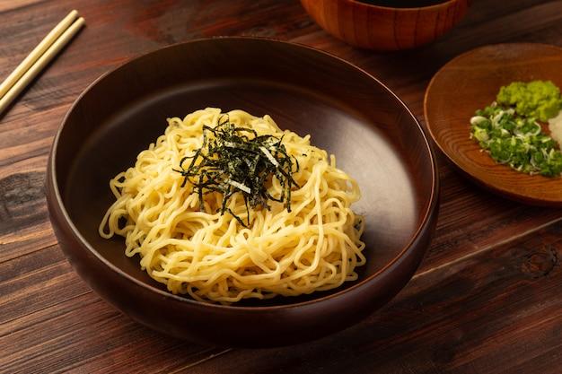 """Japoński zimny makaron ramen lub """"zaru soba"""" z posiekaną zieloną cebulą, tartym wasabi i filiżanką do sosu"""
