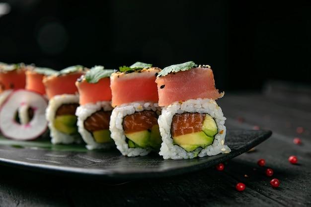 Japońskie bułeczki z łososiem i tuńczykiem na drewnianym stole