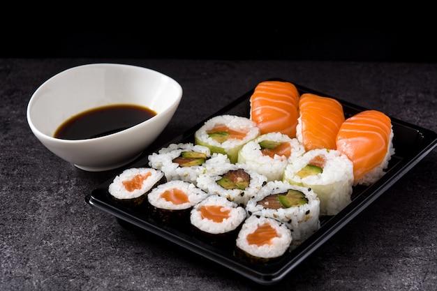 Japońskie jedzenie: maki i nigiri sushi ustawiają czarne tło