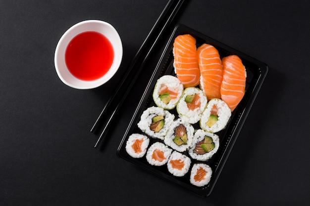 Japońskie jedzenie: maki i nigiri sushi ustawione na czarno, widok z góry