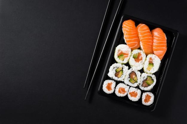 Japońskie jedzenie: maki i nigiri suszi ustawiający na czarnej tło odgórnego widoku kopii przestrzeni