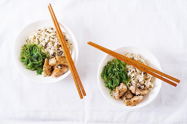 Japońskie jedzenie. miska ryżu, gotowanej białej ryby i wakame chuka lub sałatka z wodorostów. widok z góry. leżał płasko